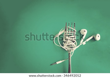 Earphones on fork on mint green background. Concept of Music. Vintage effect. - stock photo