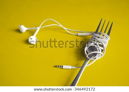 Earphones on fork on yellow background. Concept of Music. Bright color style. - stock photo