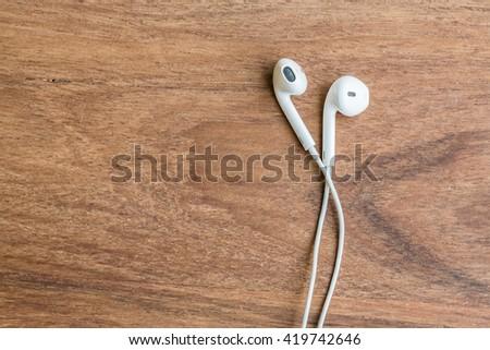earphones on wood background - stock photo