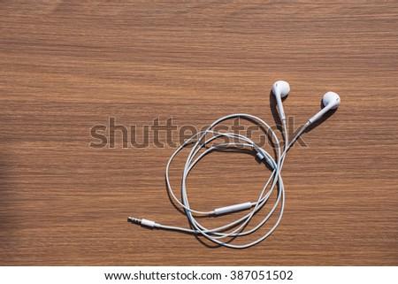 Earphones on Wooden Background - stock photo