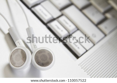 Earphones Resting On Laptop - stock photo