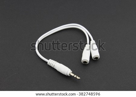 Earphones splitter cable, black background - stock photo