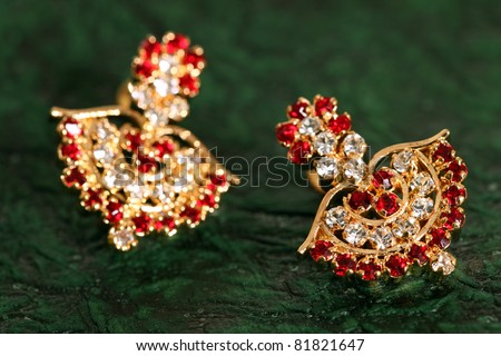 earring on textured green background. - stock photo