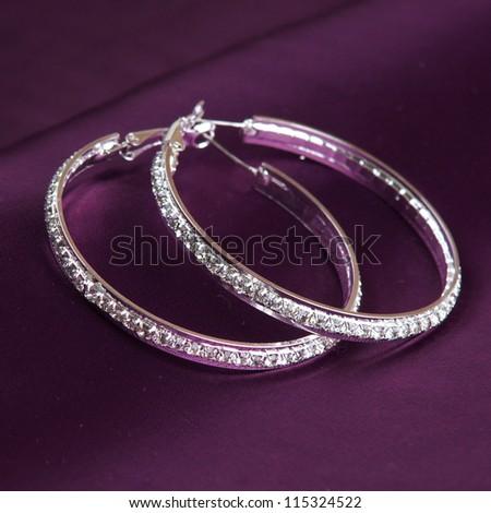 earrings on purple background - stock photo
