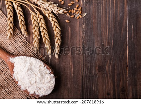 Ears of wheat and flour in the wooden spoon on the table - stock photo