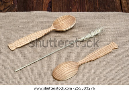 Ears of wheat and wooden spoon on the table - stock photo
