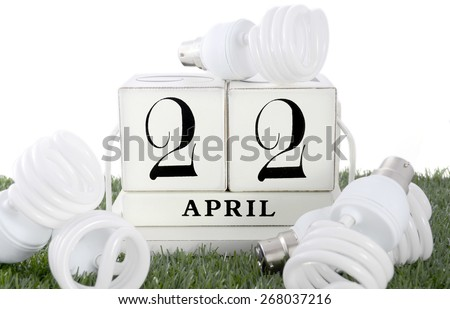 Earth Day, April 22, concept with energy saving light bulbs surrounding white wood block calendar. - stock photo