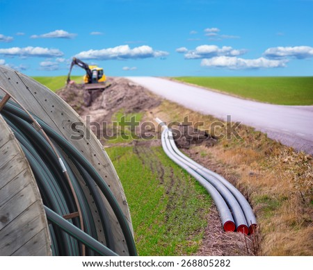 Earth digger used to dig down cables for broadband connection in rural area - stock photo