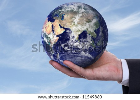 earth in a hand on background blue sky - stock photo