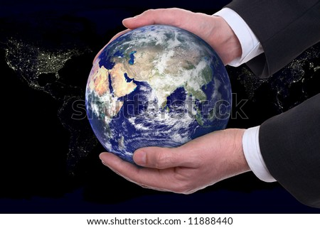 earth in a hands on background night city - stock photo