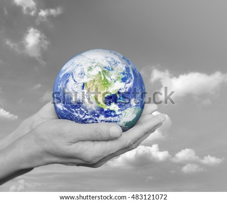 Earth in black and white hands over black and white sky with clouds, Environment concept, Elements of this image furnished by NASA