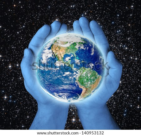 earth in blue hands on black background .Elements of this image furnished by NASA - stock photo