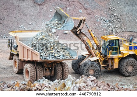 earth mover loading dumper truck with rocks in quarry. - stock photo