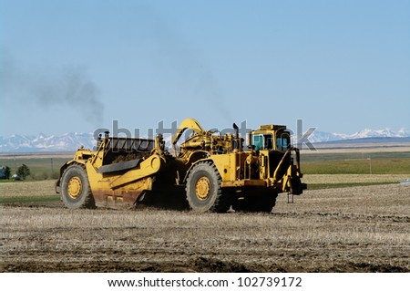 Earth movers in field - stock photo