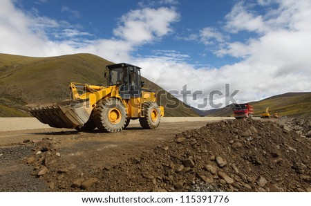 Earth movers in field with dust - stock photo