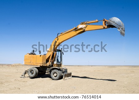 earth moving excavator on field - stock photo