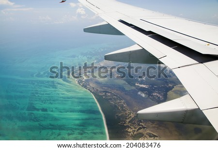 Earth, ocean and plane wing view from plane window - stock photo