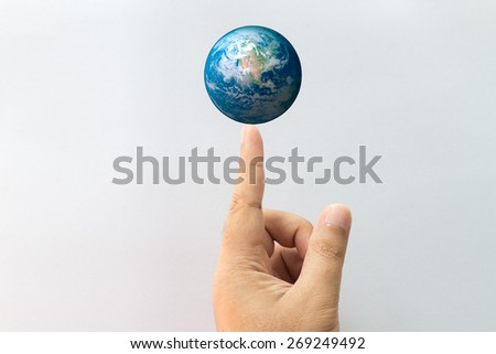 Earth on finger point Elements of this image furnished by NASA - stock photo