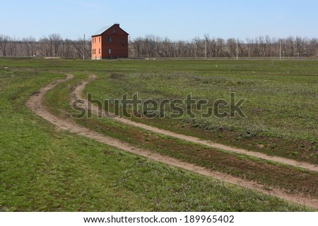 Earth road leading to a lonely red brick cottage in the spring meadow against a blue sky - stock photo