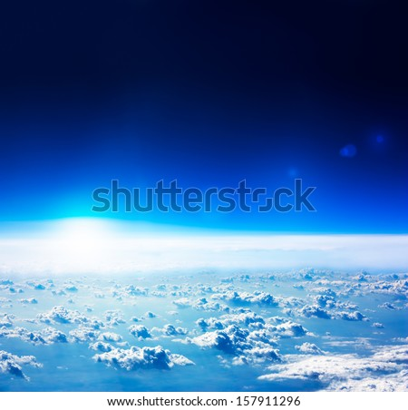 Earth View from Space. Dark Blue Sky with Rised Sun and Clouds. - stock photo