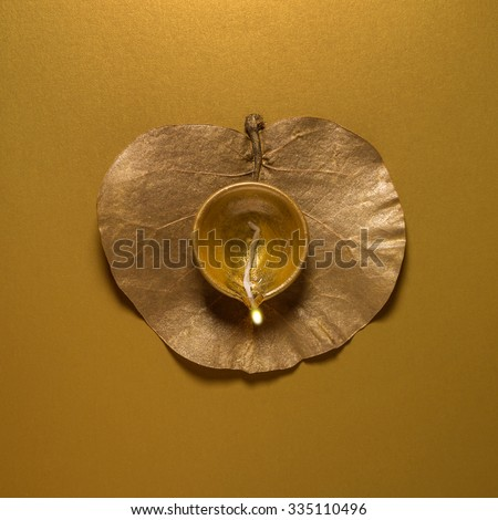Earthen oil lamp on golden dry leaf. view from above. Indian religious background. - stock photo