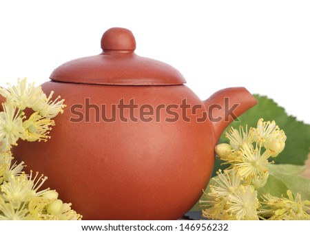 earthenware teapot with linden tea and flowers on white background - stock photo