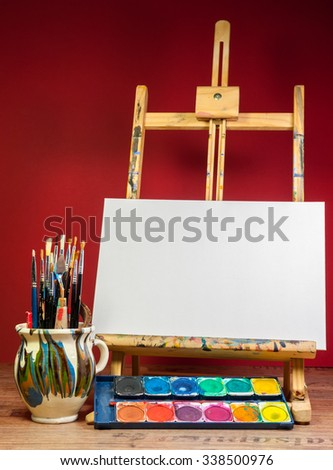easel palette watercolors and brushes with empty white canvas - stock photo