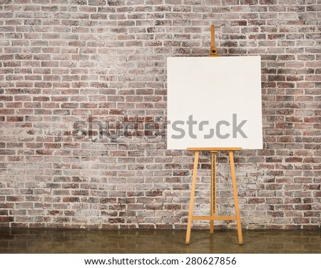 Easel with blank canvas on a brick wall background - stock photo