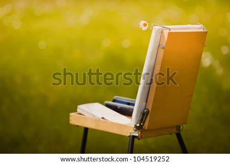 Easel with camomile in the field - stock photo