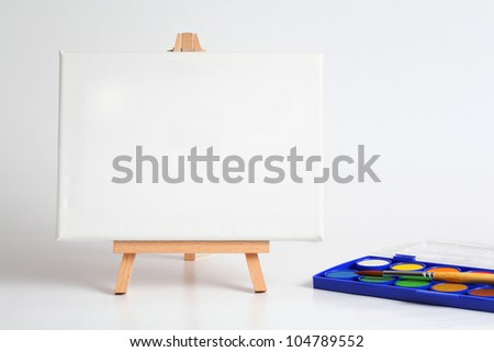easel with water color and brush. - stock photo