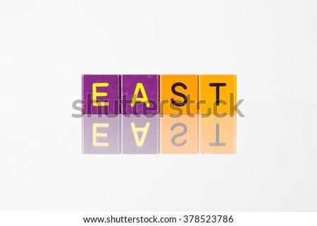 East - an inscription from children's wooden blocks - stock photo