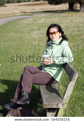 East Asian Woman seating on a bench in the Richmond Park, London, UK.   - stock photo