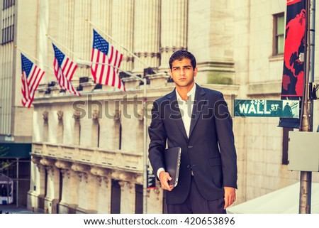 East Indian American Business Man traveling, working in New York. Wearing black suit, holding laptop computer, a student standing on Wall Street outside office building. Instagram filtered effect. - stock photo