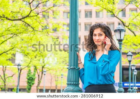 East Indian American Business Woman Calling Outside in spring day. Wearing long sleeve, V neck shirt, a beautiful college student standing by light pole, smiling, listening, talking on mobile phone.  - stock photo