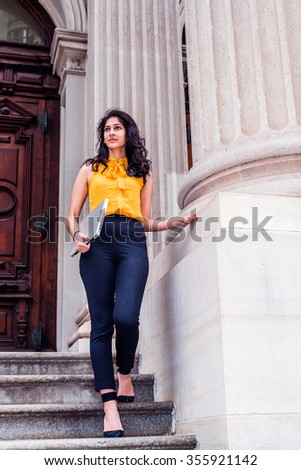 East Indian American college student studying in New York, wearing sleeveless orange shirt, striped pants, high heels, carrying laptop computer, walking down stairs. Filtered look with purple tint. - stock photo