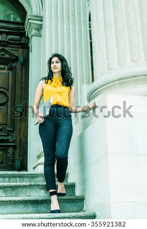East Indian American college student studying in New York, wearing sleeveless orange shirt, striped pants, high heels, carrying laptop computer, walking down stairs. Filtered look with green tint..  - stock photo