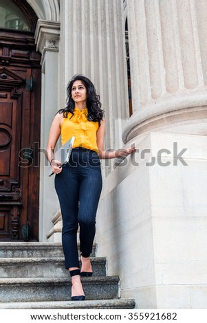 East Indian American college student studying in New York, wearing sleeveless orange shirt, striped pants, high heels, carrying laptop computer, walking down stairs. Filtered look with dark blue tint. - stock photo