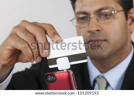 East Indian businessman using a credit card payment swiper on his Smart Phone - stock photo