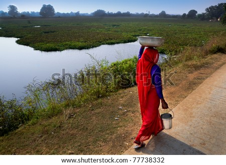East Indian woman covered in red sari walks to get water for small village. - stock photo
