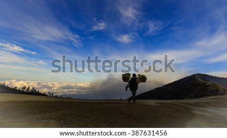 East Java, Indonesia - June 19, 2015: The silhouette of Volcanic Sulfur Miner in Ijen Crater, who carrying about 60-90kg of sulfur stone to the market - stock photo