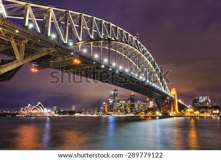 East side of Sydney harbour bridge at sunset with bright illumination of steel arch and columns reflecting in the blurred waters of harbour with Sydney city CBD in the background