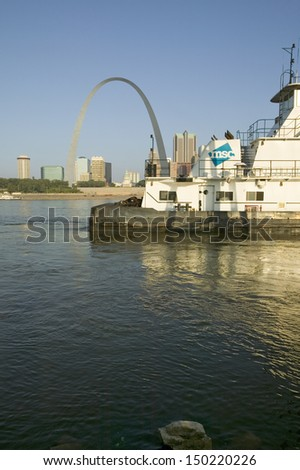 EAST ST. LOUIS, ILLINOIS - CIRCA 2006: Daytime view of tug boat pushing barge down Mississippi  River in front of Gateway Arch and skyline of St. Louis, USA - stock photo