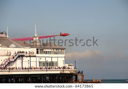 EASTBOURNE, ENGLAND - AUGUST 16: Royal Air Force display team The Red Arrows perform over the Victorian pier at an airshow on August 16, 2009 in Eastbourne, East Sussex. The display is held annually.