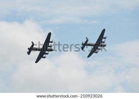 EASTBOURNE, ENGLAND - AUGUST 14, 2014: The last two flying Lancaster bombers display at the Airbourne airshow. PA474 (front) of the Battle of Britain Memorial Flight was joined by KB726 from Canada. - stock photo