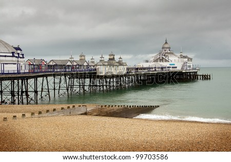 Eastbourne pier and beach. English seaside victorian amusement arcade and tourist landmark. - stock photo