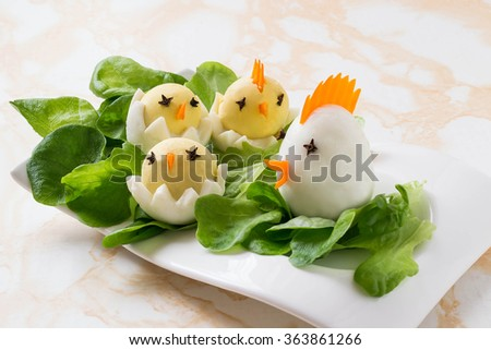 Easter appetizer of boiled eggs in the form hen with chicks on lettuce leaves - stock photo