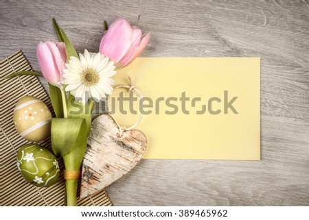 "Easter arrangement with flowers and eggs on wood with caption ""Happy Easter!"" - stock photo"
