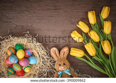 Easter background, eggs, rabbit, yellow tulips. Hand painted decorated eggs, happy bunny, spring flowers on wood, copy space.  Still life, top view.Unusual creative holiday greeting card  - stock photo
