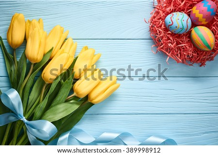 Easter background, eggs with yellow tulips. Hand painted multicolored decorated eggs in straw nest and spring flowers, wood, copy space.  Still life, top view. Unusual creative holiday greeting card  - stock photo