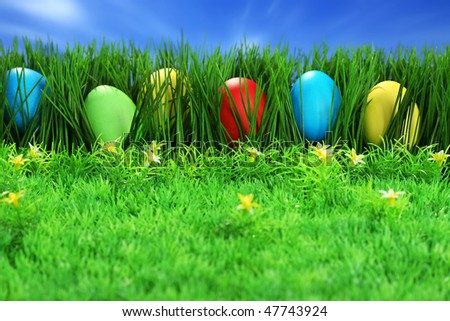 Easter background, multi-coloured eggs, grass and blue sky - stock photo